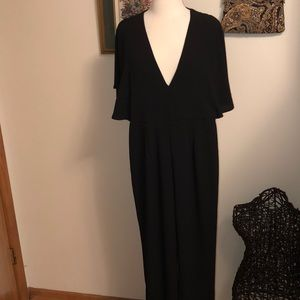Black jumpsuit with cape sleeves, open draped back